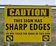 Sign reading 'caution this sign has sharp edges'